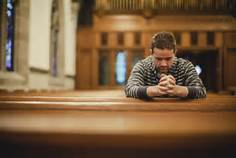 man praying, in pew 2