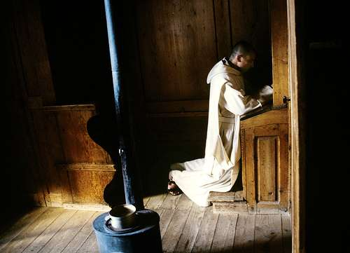 monk kneeling at prayer